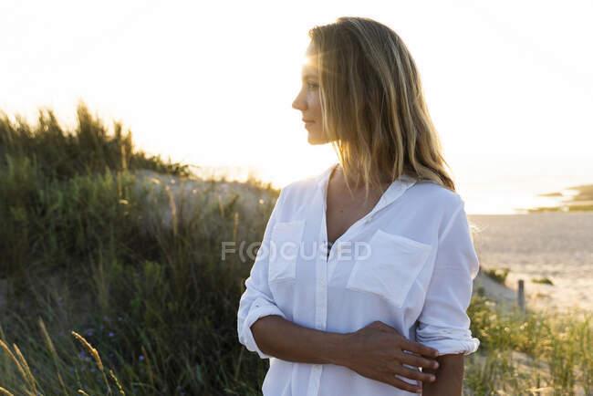 Mulher adulta média olhando para longe enquanto estava em pé pela duna de areia — Fotografia de Stock