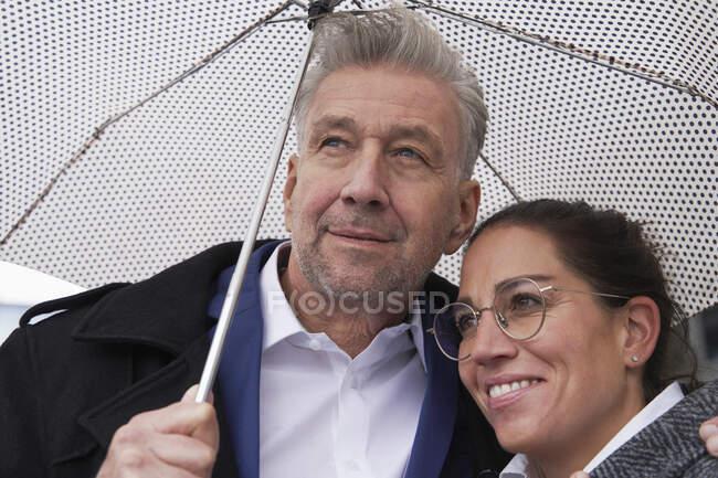 Посмішка бізнесмена з старшим бізнесменом стоїть під парасолькою під час сезону дощів. — стокове фото