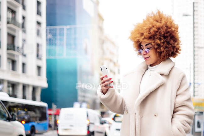 Woman with afro blond hair using smart phone while standing on street — Stock Photo
