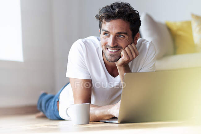 Thoughtful man with laptop lying on floor at home — Stock Photo