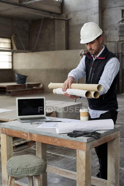 Male engineer holding blueprints while standing at table in building — Stock Photo