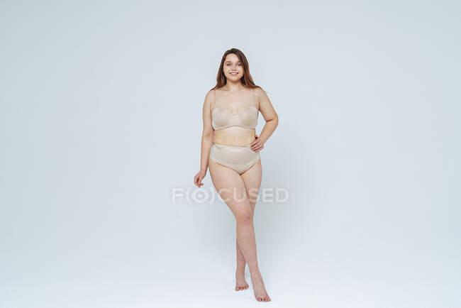 Mujer segura sonriendo mientras está de pie con la mano en la cadera en el estudio - foto de stock