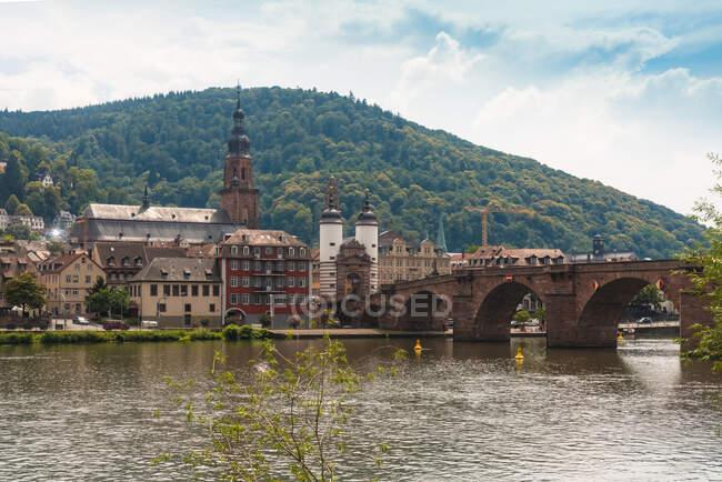 Alemania, Baden-Wurttemberg, Heidelberg, Karl Theodor Puente que cruza el río Neckar con edificios de la ciudad vieja en el fondo - foto de stock