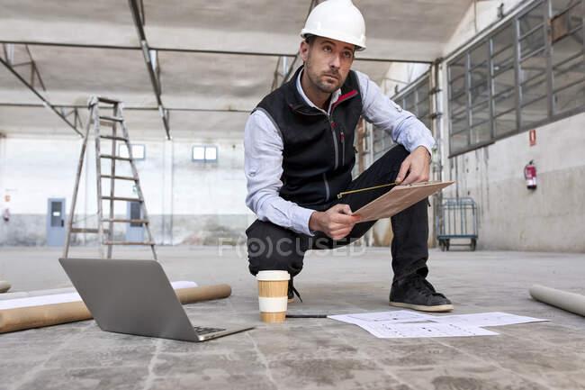 Architecte masculin tenant le plan du site tout en s'accroupissant sur le sol dans le bâtiment — Photo de stock