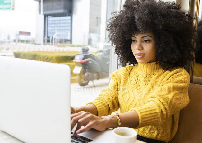 Young woman working on laptop while sitting at cafe — Stock Photo