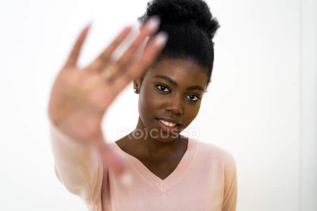 Mujer mostrando gesto de stop mientras está de pie sobre fondo blanco - foto de stock