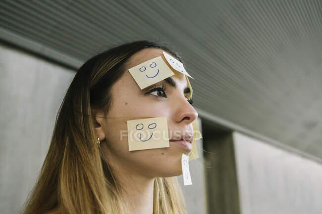 Портрет серйозної жінки, одягненої в клейкі ноти на обличчі. — стокове фото