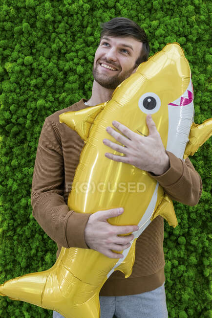 Smiling male entrepreneur day dreaming while holding inflatable shark against green backdrop — Stock Photo