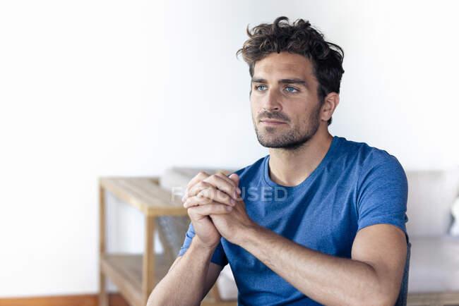 Homem pensativo olhando para longe enquanto sentado com as mãos apertadas em casa — Fotografia de Stock