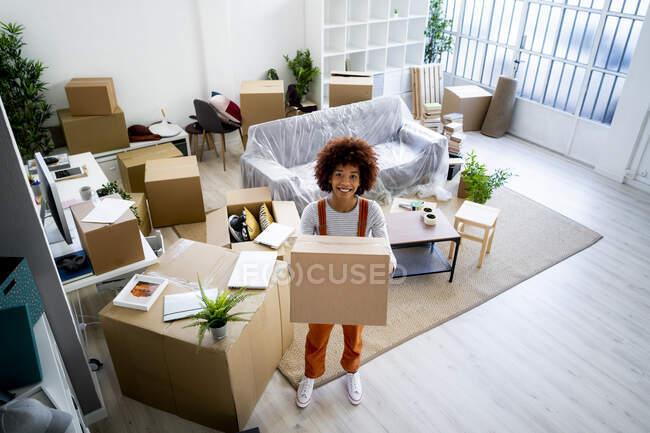 Joyeux jeune femme afro portant le carton tout en déménageant dans une nouvelle maison — Photo de stock