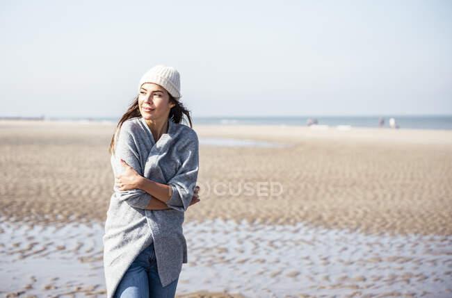 Mujer joven en jersey de cárdigan contemplando mientras camina en la playa - foto de stock