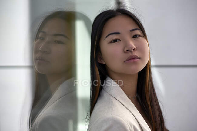 Confident woman against glass wall — Stock Photo