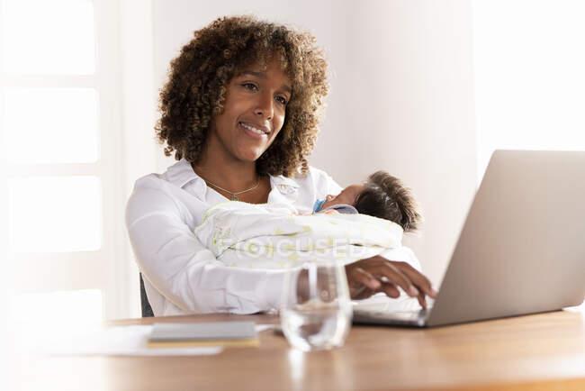 Sonriente madre sentada con el bebé mientras trabaja en el ordenador portátil en casa - foto de stock