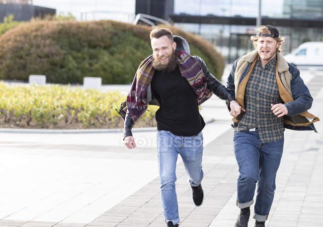 Gay namorados de mãos dadas enquanto correndo no rua no cidade — Fotografia de Stock