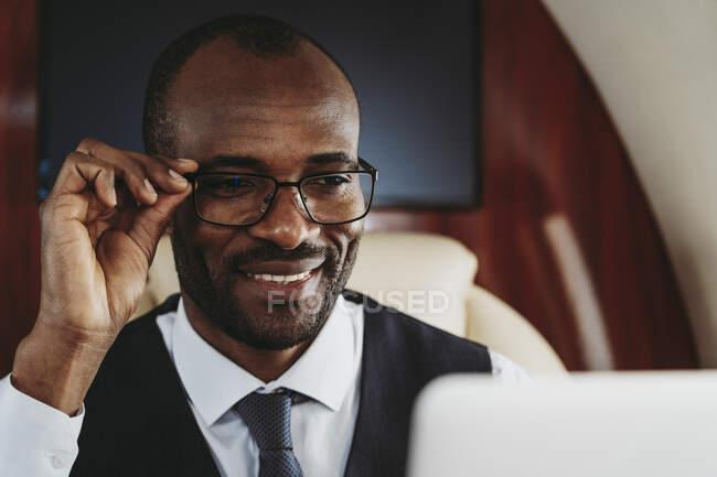 Усміхаючий бізнесмен тримає окуляри в літаку. — стокове фото