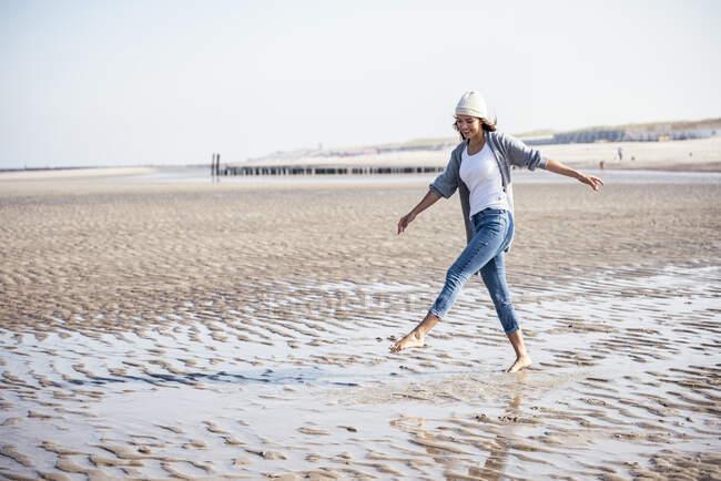 Mujer joven despreocupada en sombrero de punto caminando sobre arena mojada en la playa - foto de stock