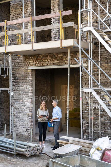 Безробітна жінка з цифровим планшетом обговорює питання, стоячи біля колеги на будівельному майданчику. — стокове фото