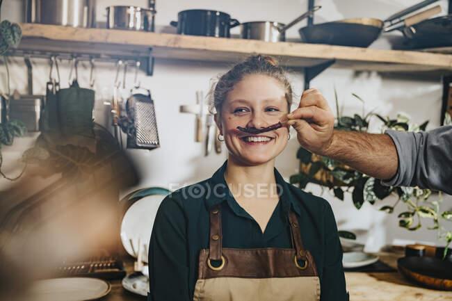 Шеф робить вуса сухого чілі колегам, стоячи на кухні. — стокове фото