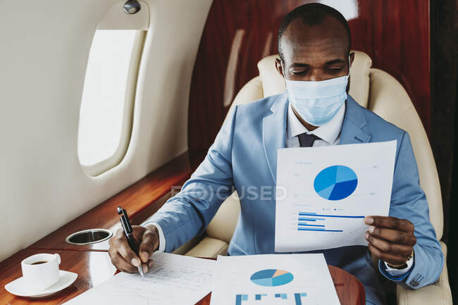 Young businessman analyzing graph while working in airplane during COVID-19 — Stock Photo