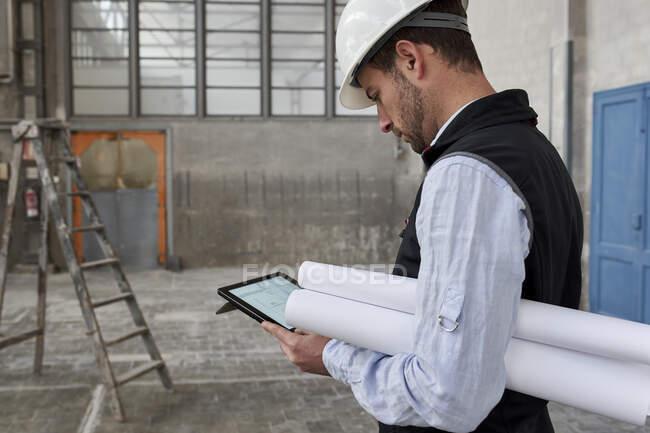 Architecte masculin avec des plans en utilisant une tablette numérique tout en se tenant debout dans le bâtiment — Photo de stock