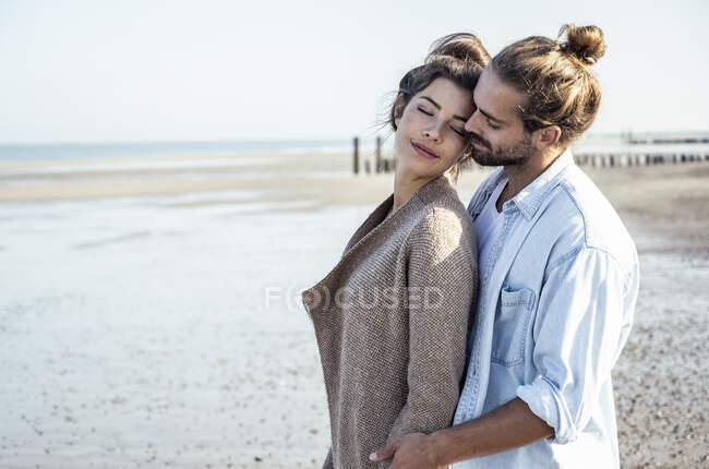 Ласковая молодая пара на пляже в солнечный день в выходные — стоковое фото