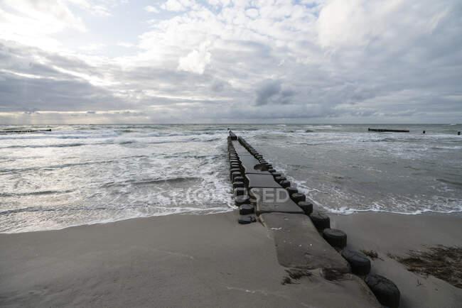 Groyne en la playa costera al anochecer nublado - foto de stock