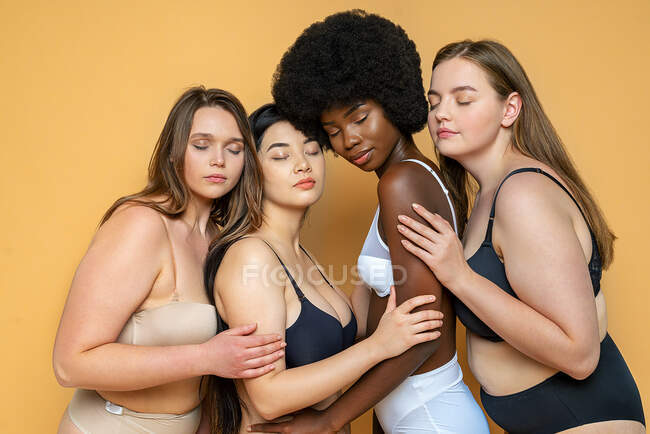 Multi-ethnic group of female models in lingerie with eyes closed embracing each other by yellow background — Stock Photo