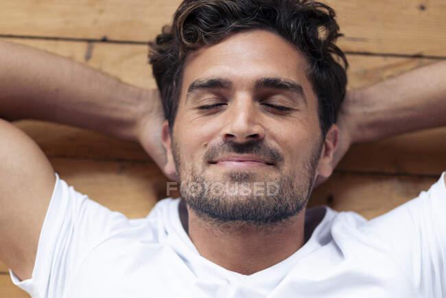Hombre sonriendo mientras se relaja en el suelo en casa - foto de stock