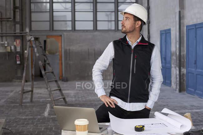 Arquiteto masculino contemplando enquanto está à mesa no edifício — Fotografia de Stock