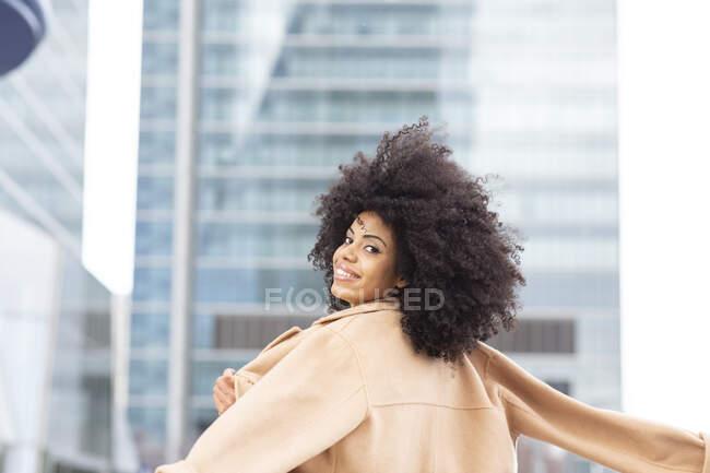 Щаслива жінка грає з курткою, стоячи надворі. — стокове фото