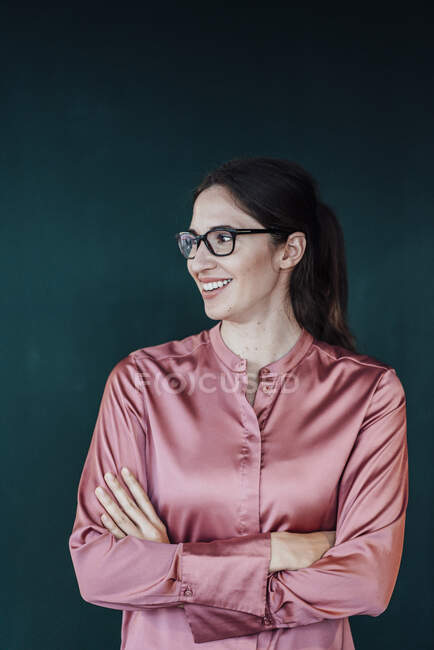 Female professional with arms crossed looking away against green background in studio — Stock Photo