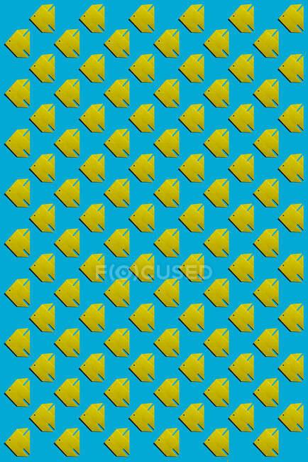 Patrón de peces de origami amarillo sobre fondo azul - foto de stock