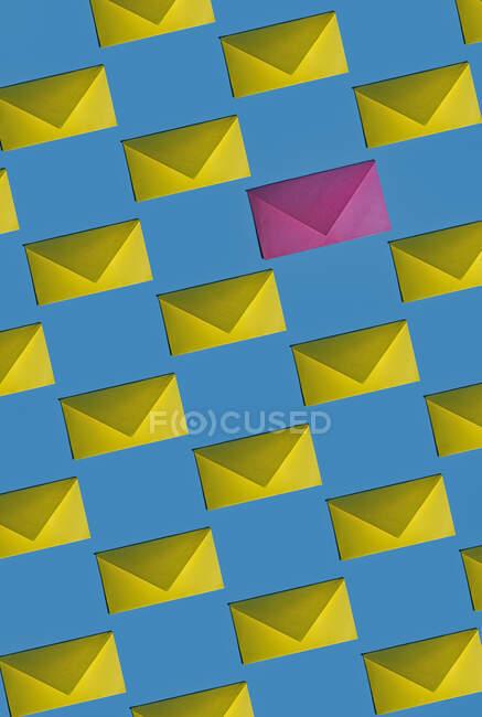Patrón de filas de sobres amarillos con un solo rosa - foto de stock