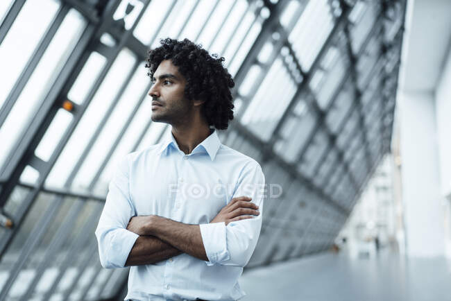 Thoughtful young male professional standing with arms crossed while looking away at workplace — Stock Photo