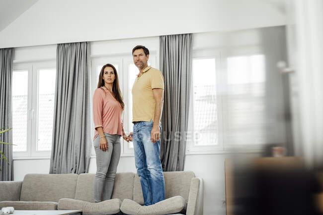Зрелая пара, держащаяся за руки, стоя на диване в квартире — стоковое фото