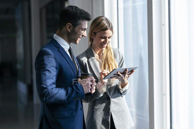 Безробітна жінка посміхається, користуючись цифровим планшетом, стоячи біля колеги в офісі. — стокове фото