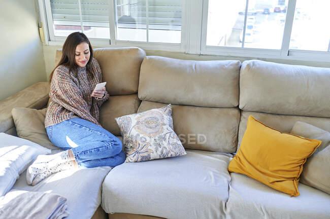 Mujer sonriente usando el teléfono móvil mientras está sentada en el sofá en casa - foto de stock