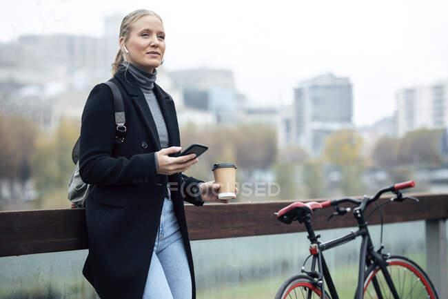 Жінка тримає мобільний телефон, слухаючи музику за допомогою навушників на велосипеді. — стокове фото