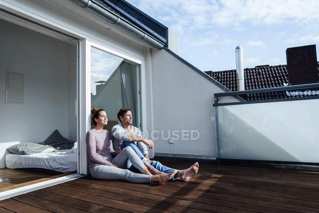 Sonriendo hombre y mujer maduros relajándose con los ojos cerrados en el balcón en el día soleado - foto de stock