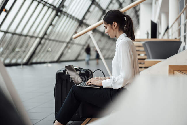 Businesswoman working on laptop while sitting in office corridor — Stock Photo