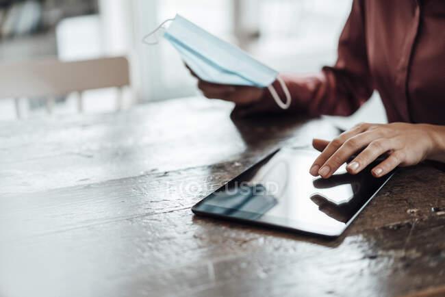 Mão de empresária feminina usando tablet digital à mesa no café durante pandemia — Fotografia de Stock