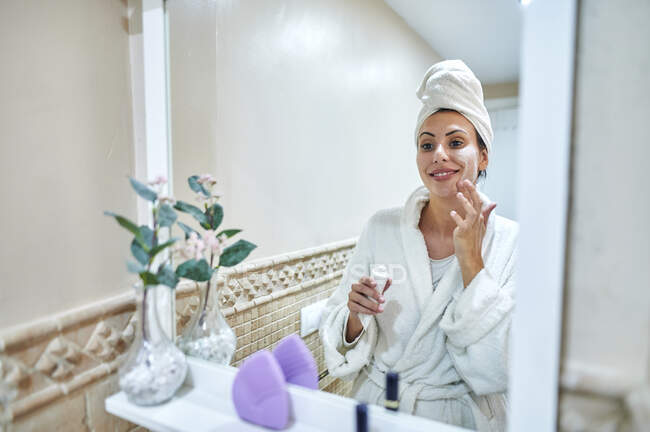 Smiling woman applying face cream while looking at mirror in bathroom — Stock Photo