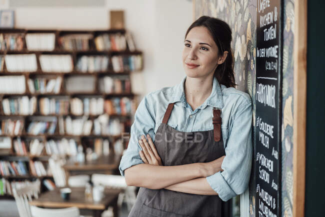 Думливий жіночий підприємець зі схрещеними руками дивиться у кав'ярню — стокове фото