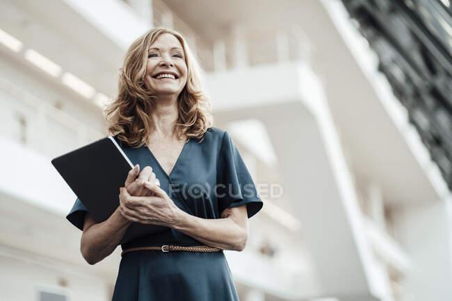 Щаслива жінка-підприємець з ноутбуком на коридорі в офісі — стокове фото