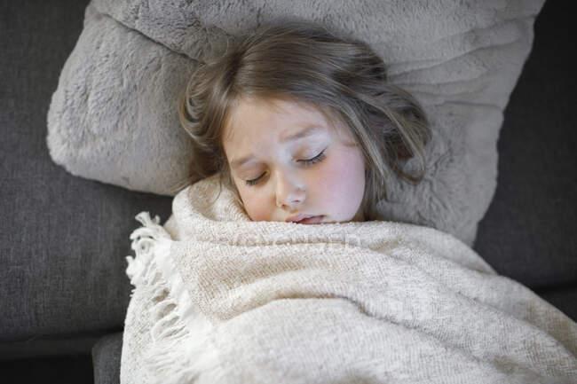 Niña enferma durmiendo con manta en el sofá en casa - foto de stock