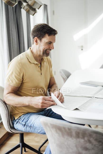 Счастливый зрелый мужчина переворачивает страницу газеты на столе дома — стоковое фото