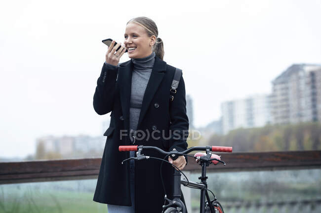 Усміхнена жінка розмовляє по мобільному телефону, тримаючи велосипед проти неба. — стокове фото
