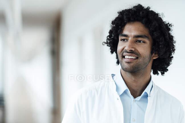 Sorridente operatore sanitario maschile con i capelli ricci neri guardando dall'ospedale — Foto stock