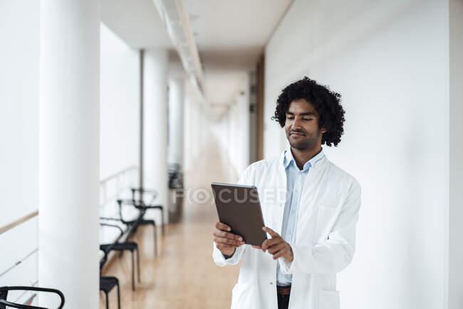 Confiado joven médico masculino usando tableta digital en el pasillo del hospital - foto de stock