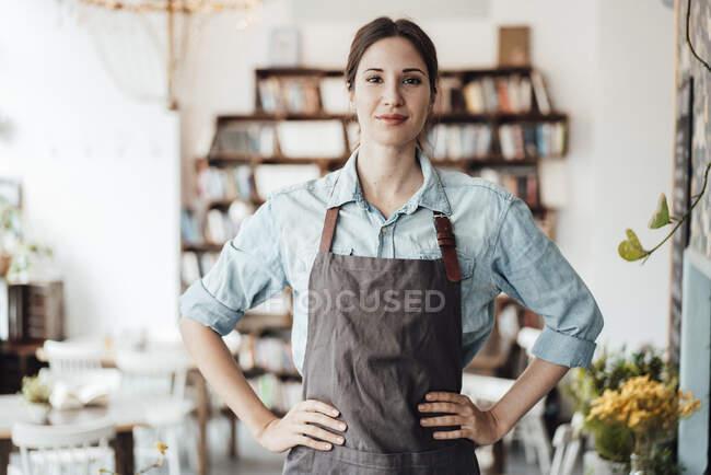 Довірлива жінка-менеджер з рукою на стегно стоячи в кафе — стокове фото